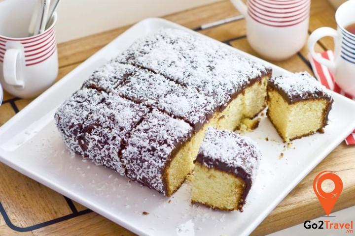 Lamington được làm từ cốt gato rồi phủ lên một lớp socola ấm mịn và được khoác thêm lớp áo dừa trắng tinh, thơm ngọt