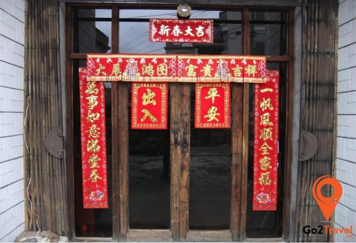 Dán giấy đỏ cắt truyền thống lên cửa sổ