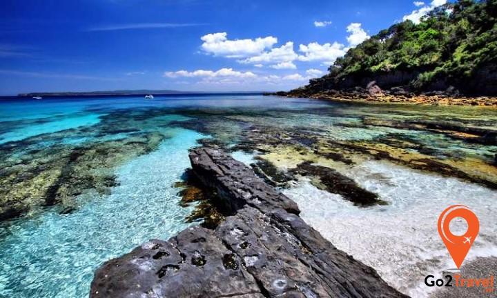 bờ biển sóng vỗ nhẹ nhàng vào bãi cát trắng mịn trải dài