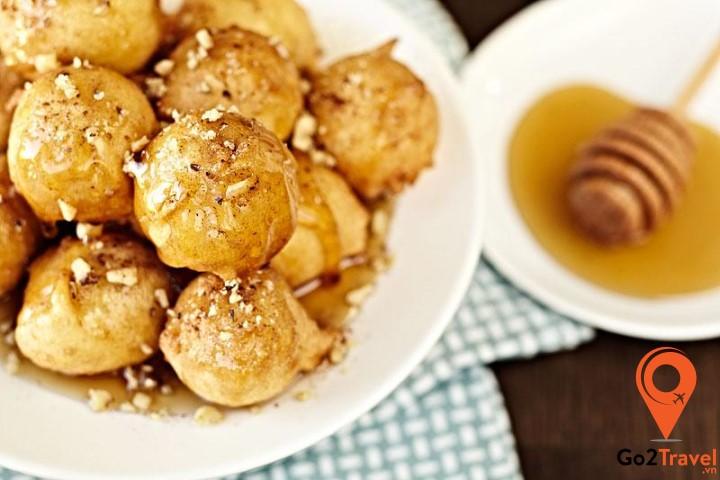 Loukomades là món ăn này nổi bật với hương thơm từ caramel với những viên bột chiên giòn, được tắm trong mật ong