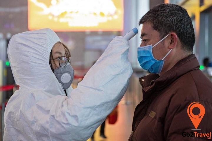 bác sĩ đang kiểm tra thân nhiệt của bệnh nhân nghi nhiễm corona